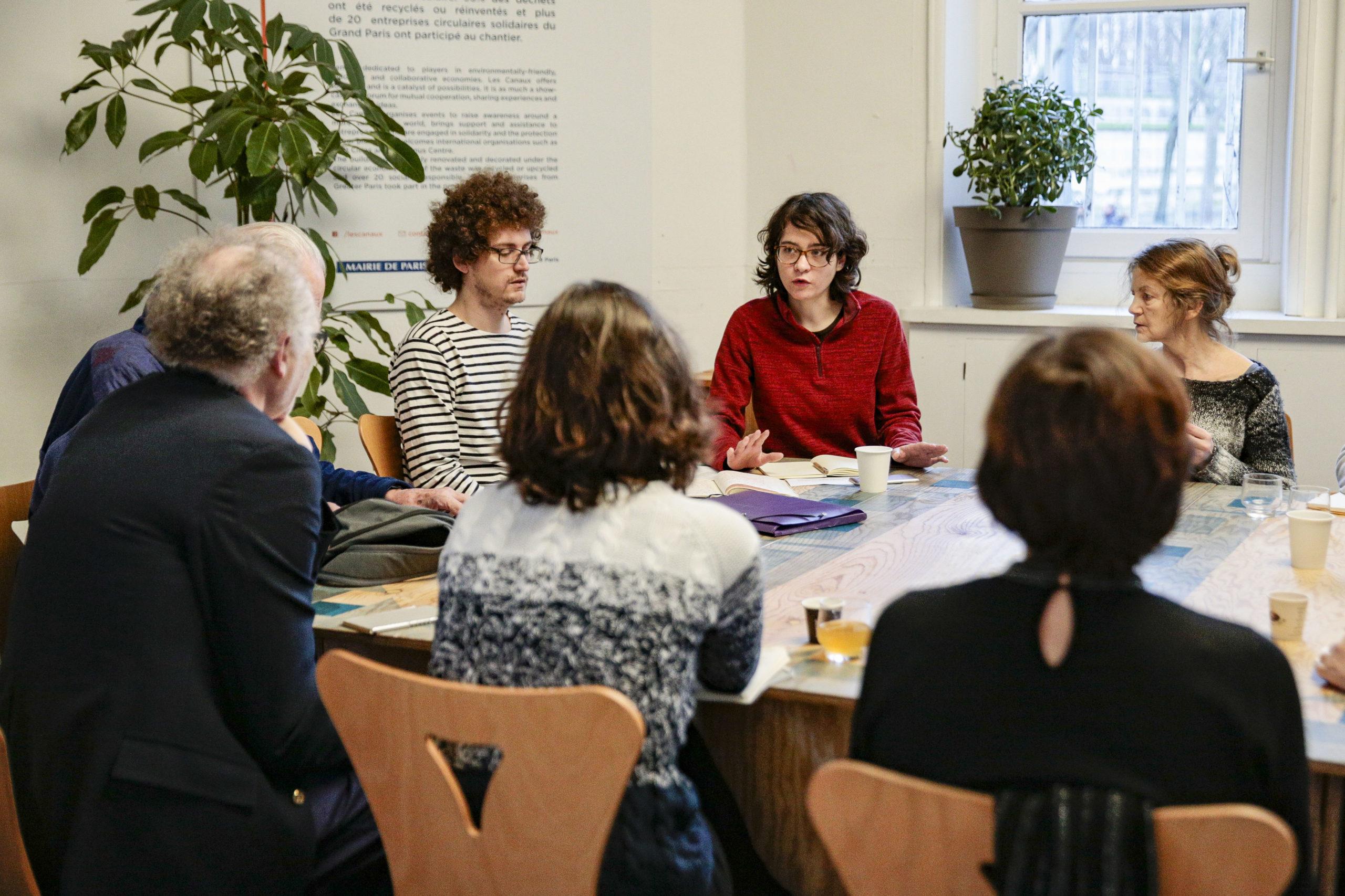 Plusieurs personnes autour d'une table. Une personne parle.